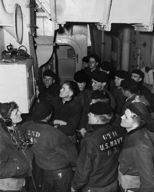 Official U.S. Navy photograph of crew members of the USS Augusta List listening to Browns battle report during World War II